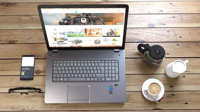 Stôl, na ktorom je notebook, káva, mobil a okuliare.jpg