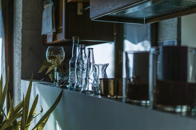 Sklenené poháre, fľaše, digestor a zelený kvet v kuchyni