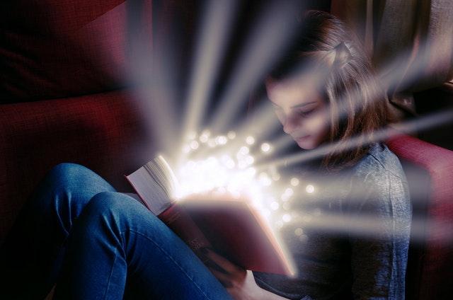 Dievča číta knihu, z ktorej vyžaruje svetlo.jpg