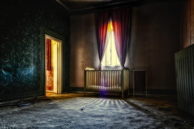 Tmavá izba s detskou postieľkou a veľkým oknom cez ktoré presvitá svetlo.jpg